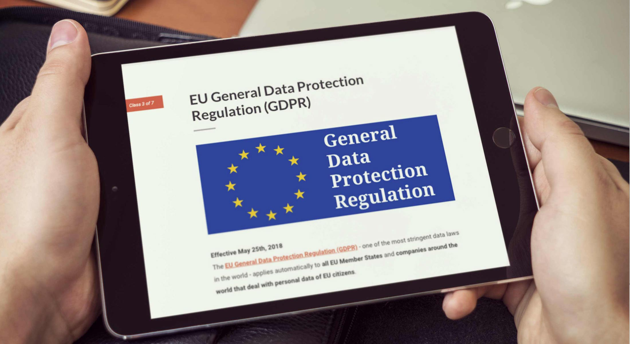 Hands holding tablet with a responsive elearning course page about the General Data Protection Regulation